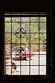 View of brightly painted car through window with metal lattice
