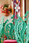 Backrests of turquoise peacock chairs with many curlicues