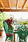 Cheerful woman on Mediterranean terrace with turquoise peacock armchairs