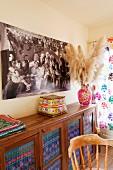 Eine Anrichte aus Holz, mit bunt gemustertem Stoff in den Scheiben, Foto einer Hippie-Familie und Ethno-Accessoires
