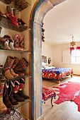 Cowboy boots on shoe rack an view into ethnic-style bedroom through painted archway