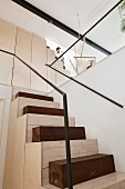 Custom staircase made from pale wood, dark wooden blocks and minimalist metal handrail