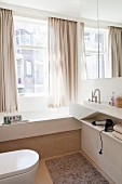 Bright, modern bathroom with custom washstand and fitted bathtub next to window