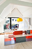Designer table and bench set with interior painted in bright colours in front of glass gable-end wall with view of family on roof terrace