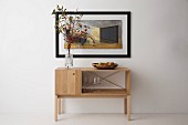 Branches of autumnal leaves on simple, timeless sideboard below picture