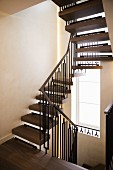 Winding metal staircase with wooden treads and handrail and tall stairwell window