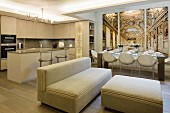 Open-plan living area in elegant beige interior with trompe l'oeil panels behind set dining table