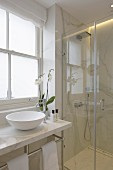 Elegant bathroom in white marble with glass shower screen and countertop basin