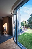 Curved glass wall with view into summery garden of architect-designed house