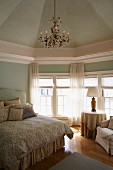 Elegant bedroom with chandeliers and walls and ceiling painted pastel green