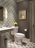 Bathroom with toilet and matching geometric wallpaper and floor tiles