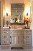Elegant, romantic washstand below opulent, country-house-style mirror