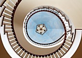 View up through stairwell of elegant, winding staircase with trompe l'oeil ceiling painted to resemble sky