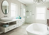 Elegant bathroom with free-standing bathtub, long washstand, oval mirror and glazed shower in corner