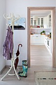 Coat stand and wellingtons in hall next to doorway leading into white fitted kitchen