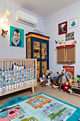 Rug with animal motifs, cot and soft toys on painted wardrobe in cheerful, bright child's bedroom