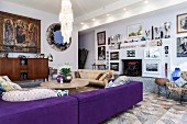 Indigo sofa, round coffee table, framed pictures and collection of trophies in modern interior