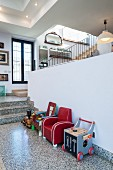 Retro children's armchairs and toys in front of half-height wall in open-plan interior with terrazzo floor