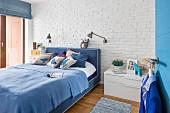 Doppelbett in Blautönen vor weiss geschlemmter Backsteinwand im Schlafzimmer