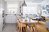 Fitted kitchen with integrated dining area and adjoining living area in shades of pale grey