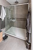 Geräumige Duschkabine mit Glasschiebetür und durchgehender Ablagefläche in Wandnische