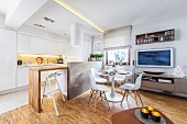 Classic dining area in front of open-plan, white fitted kitchen with engineered wood counter