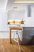 Designer bar stool at kitchen counter with solid-wood top in front of white fitted kitchen