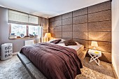 Bedroom with long-pile carpet and fabric-covered panelled wall; double bed with upholstered frame
