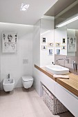 Modern pictures in designer bathroom with ample storage space in fitted cupboards and washstand base unit