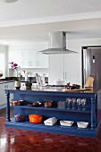 Blue-painted island counter with open-fronted shelved in modern, white fitted kitchen