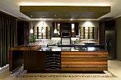 Illuminated island counter with integrated wine rack and swivelling kitchen trolley
