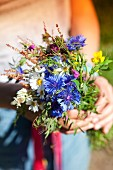 Woman holding bunch of wild flowers