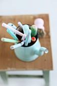 Handles of pastel wooden spoons stored in vintage jug