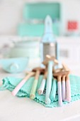 Vintage wooden spoons in pastel shades on turquoise, lacy doily