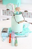 Nostalgic still-life arrangement of pastel kitchen utensils in vintage milk can
