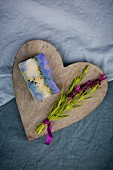 Bar of handmade lavender soap and sprig of fresh lavender on wooden heart
