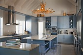 Modern kitchen with stone worksurfaces and pale blue cupboards; driftwood chandelier above island counter