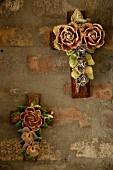 Christliches Kreuz mit bemalten Blumen aus Keramik an unverputzter Wand aufgehängt