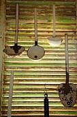 Verschiedene Schöpflöffeln an Fensterladen mit Lamellen