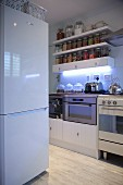 White fridge-freezer opposite kitchen counter and storage jars on wall-mounted shelves