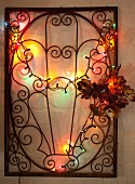 Wrought iron lattice decorated with flowers and fairy lights hung on wall