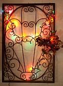 Schmiedeeisernes Gestell mit Blumendeko und brennender Lichterkette, an Wand aufgehängt