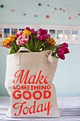 Tulips in shopping bag with printed motto