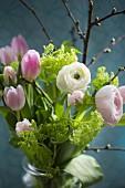 Tulips, viburnum, ranunculus and cherry twigs in jar of water