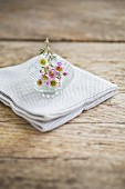 Waxflowers in glass dish on folded cloth