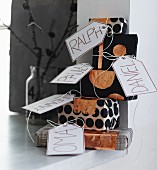 Stack of gifts wrapped in black and white paper with copper accents and name tags