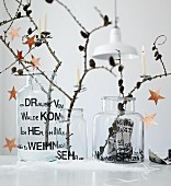 Larch branches with cones and stars arranged in three old glass vases decorated with adhesive letters