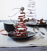 Christmas tree ornaments made from coiled copper wire, bells and cinnamon stars decorating table