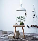 Kleiner Tannenbaum auf Holzhocker, Geschenke in Packpapier und ein Mobile aus Tannenzapfen