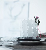 Festive hand-made table centrepiece: candle lantern wrapped in cut-out paper cover